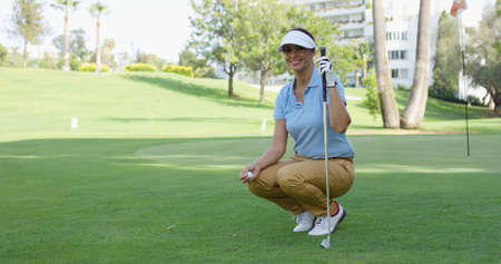 Smiling female golfer with brown hair crouches with club and holds ball while on green lawn