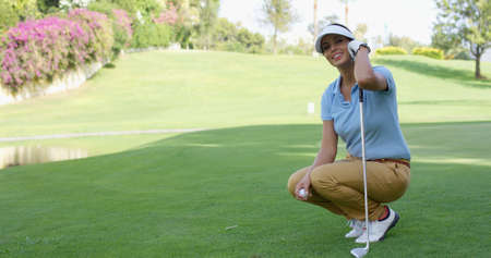 crouches: Smiling female golfer with brown hair crouches with club and holds ball while on green lawn