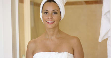 shower stall: Beautiful young adult woman leaning at entrance of shower stall or sauna while wrapped in towels