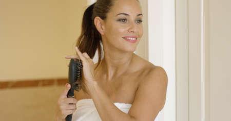 cola mujer: joven cepillarse el pelo largo y casta�o atado en una cola de caballo como ella est� en el cuarto de ba�o envuelta en una toalla blanca y limpia