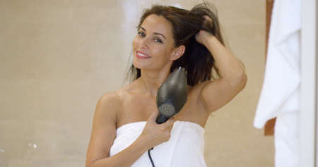 dark brown hair: Young woman standing wrapped in a towel drying her long dark brown hair with a hair dryer in the bathroom