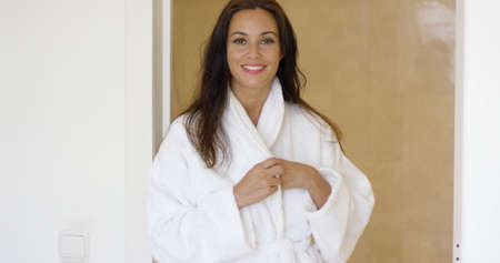 bath robe: Gorgeous female adult in white bath robe adjusting the lapels while standing near bathroom entrance