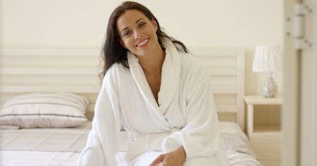 femme brune sexy: Bonne jeune femme sympathique dans un peignoir de bain blanc, assis sur le bout de son lit le matin souriant à la caméra Banque d'images