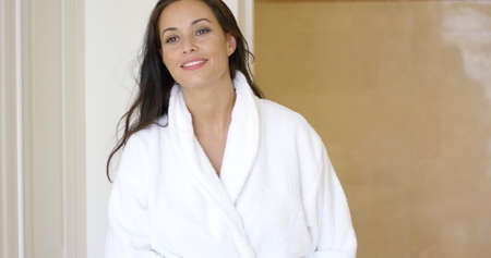 bath robe: Pretty female adult in white bath robe near bathroom entrance moving hair to side with other hand in pocket