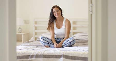 mujer en la cama: Sonriendo mujer adulta joven sola en pijama a cuadros sentado en la cama con dos almohadas detrás de ella