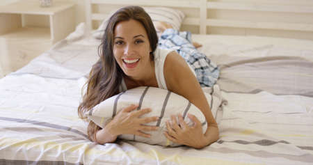 Laughing playful young woman relaxing lying on her bed in her sleep wear looking up at the camera with a vivacious smile