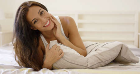 Happy young woman cuddling up in bed hugging the pillow to her chest as she grins at the camera with a friendly smile Stock Photo