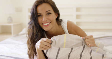 Happy attractive young brunette woman relaxing on her bed lying on her stomach with the pillow to her chest smiling at the camera