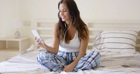 woman in bed: Smiling pretty woman listening to music at home sitting cross-legged on her bed in her sleepwear with her mobile phone