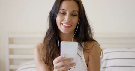 selects: Beautiful young woman listening to music on a storage device or mobile phone smiling with pleasure as she selects a tune