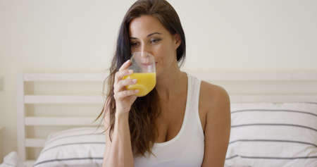 glass bed: Young woman enjoying a glass of orange juice in the morning as she relaxes sitting on her bed in a healthy diet concept