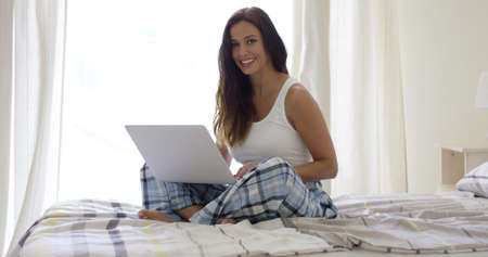 blue plaid: Single smiling woman in blue plaid pajama pants sitting cross legged while using her open laptop computer