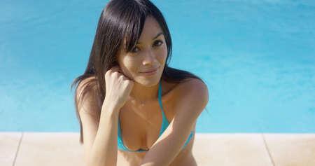 busty: mujer joven tetona y con un pelo largo morena sentada en el borde de una piscina en un bikini sonriendo a la cámara con espacio de copia.