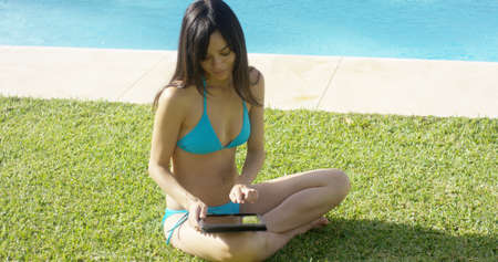 mujeres sentadas: Mujer bonita joven en un bikini sentada en la hierba usando una tableta a la piscina del complejo con una sonrisa feliz en el sol del verano