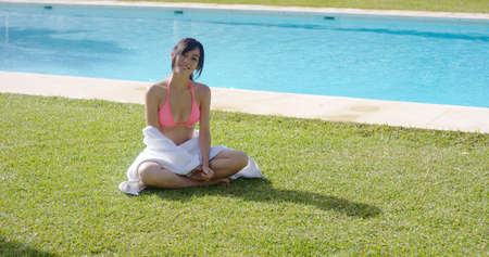 Friendly young woman relaxing on the green grass near a swimming pool with a white towel draped around her waist smiling at the camera in the summer sun. Stock Photo