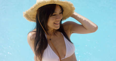 Happy trendy young woman on summer vacation sitting at the edge of a swimming pool in a bikini and sarong holding her straw sunhat with her hands. Stock Photo