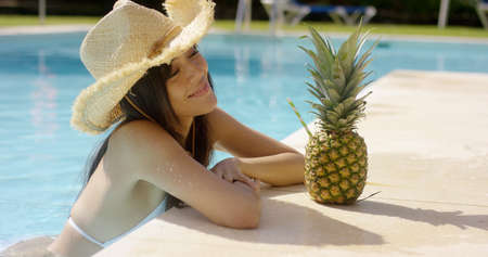 sunhat: Pretty trendy young woman in a summer pool at a tropical resort leaning on the tiled surround in a sunhat smiling at the camera with a fruity cocktail in a pineapple alongside. Stock Photo
