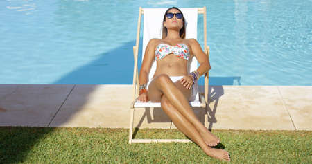 pool deck: Relaxed pretty young woman wearing sunglasses and a bikini sitting sunbathing in a deck chair at the edge of a swimming pool