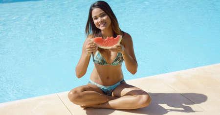 niñas en bikini: del bikini linda mujer sonriente vestida en la parte superior del bikini en el borde de la piscina clara de color azul con una rebanada de sandía parcialmente comida Foto de archivo