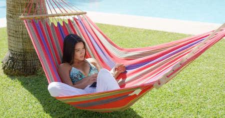 bikini top: Beautiful single young adult woman in bikini top and white pants seated comfortably in colorful hammock near swimming pool reading a book