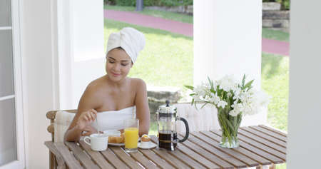 white towel: Grinning beautiful young woman wrapped in white towel at breakfast table with orange juice  pastry  coffee and bouquet outdoors