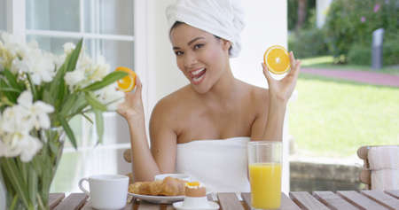 with orange and white body: Single beautiful woman with body and hair wrapped in white towels holding orange slices while seated at breakfast table outdoors Stock Photo