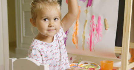 creative artist: Pretty confident little girl painting at home working on a canvas attached to an easel in her playroom turning to smile at the camera with a colorful abstract picture behind.