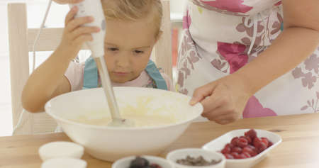 Serious pretty little girl concentrating on baking carefully holding the electric whisk to beat the ingredients in a bowl assisted by her mother