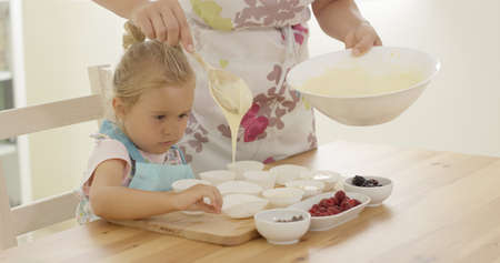 Unidentifiable parent in apron pouring muffin batter into holders on wooden table in kitchen Stock Photo