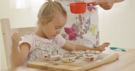 sift: Adorable female toddler watching unidentifiable woman sift sugar as it falls on freshly baked muffins in wooden tray