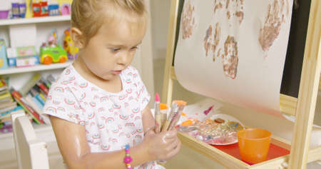 clasped hand: Cute little girl choosing a paint brush from a selection clasped in her hand as she sits at an easel painting in her playroom