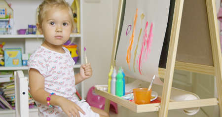earnestly: Pretty little girl artist sitting at an easel painting a colorful abstract picture with watercolors pausing to look earnestly at the camera