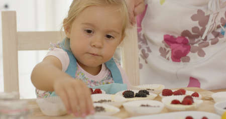 unidentifiable: Female child in blue overalls placing little berries on muffins for baking as unidentifiable woman leans on table