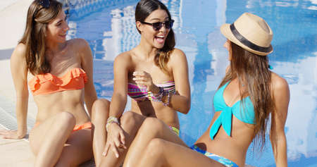 chica sexy: Tres hermosas mujeres jóvenes de moda relajantes cerca de una piscina en un sombrero y gafas de sol riendo y conversando en las vacaciones de verano