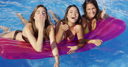 beauties: Three bikini clad beauties on a floating device blow kisses at the camera Stock Photo