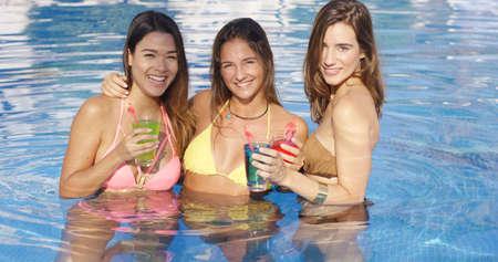 petite fille maillot de bain: Trois heureux sexy amies de détente au bras dans une piscine exploitation cocktails réfrigérés sur une chaude journée d'été