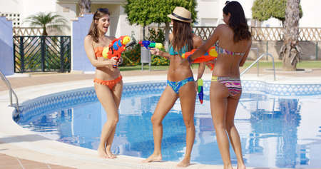 bikini pool: Three sexy young women playing with water guns at the side of a tropical swimming pool in their bikinis while relaxing on summer vacation
