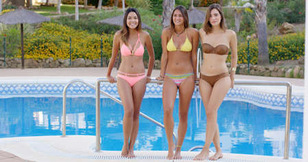 Three shapely sexy young women standing side by side in bikinis at the side of a swimming pool leaning on a rail smiling at the camera. Stock Photo