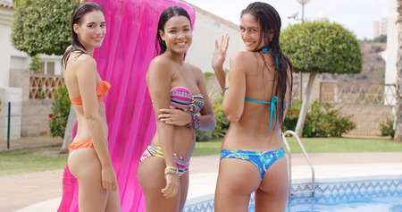 Three beautiful sexy women in bikinis standing chatting together at the edge of a pool turning to smile at the camera Stock Photo
