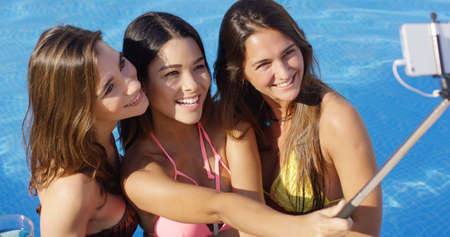 pool stick: Three young women posing close together in their bikinis taking a selfie in the pool using a selfie stick smiling and laughing