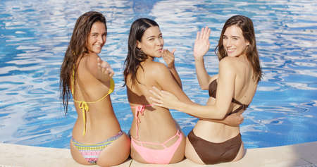 Three beauties wearing bikinis poolside wave at the camera and blow kisses