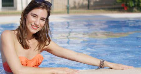 maillot de bain fille: Attrayant à la mode jeune femme avec ses lunettes de soleil sur le dessus de la tête dans une piscine se penchant sur le bord souriant à la caméra Banque d'images