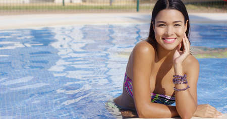 warmly: Smiling happy gorgeous young woman posing in the water at the edge of a swimming pool smiling warmly at the camera in a low cut bikini.