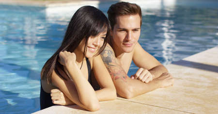 elbows: Diverse good looking couple stand in swimming pool with elbows on paved walkway as sun shines overhead Stock Photo