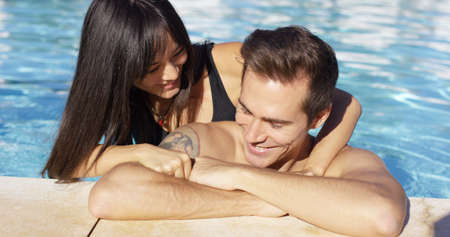 cuddled: Smiling man with tattoo is cuddled by girlfriend while standing against the paved side of a swimming pool