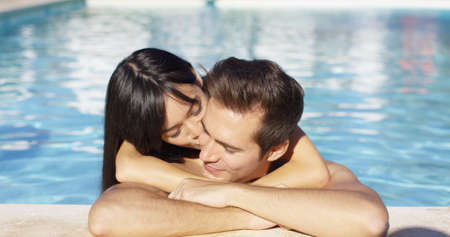 cuddles: Beautiful woman cuddles with her boyfriend in pool on a pleasant summer day