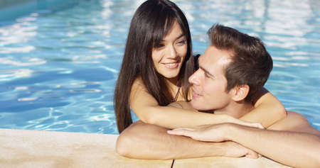 cuddles: Handsome smiling couple cuddles in swimming pool on lovely summer afternoon