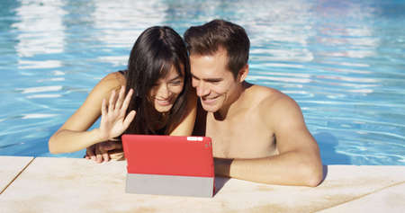 Couple communicates with friends on digital device with red cover while in swimming pool Stock Photo