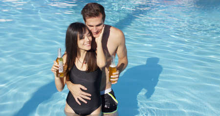 caress: Couple in swimming pool hold frothy drinks and cuddle as they smile and caress