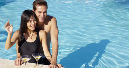 smooching: Loving couple smooching at swimming pool while keeping martini glasses with olives on the side